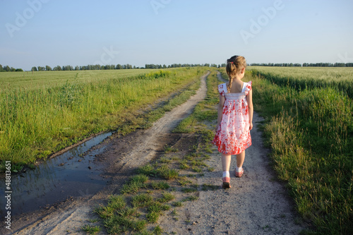 little girl walking on the road