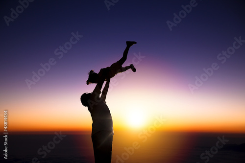 The silhouette of happy father and little girl with sunrise back