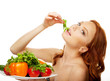 Model eating green salad from dish with vegetables