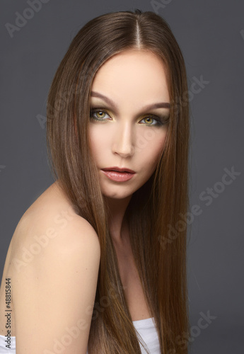 Attractive girl with long hair on gray