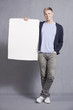 Likable man presenting white empty signboard.
