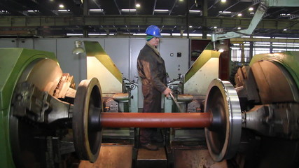 Worker processing steel on a lathe in factory