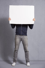 Man holding blank panel covering his face.