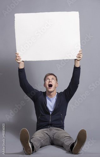 Astonished young man holding up empty panel.