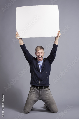 Overjoyed man holding up white empty signboard.