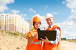 female and male construction workers looking at laptop against