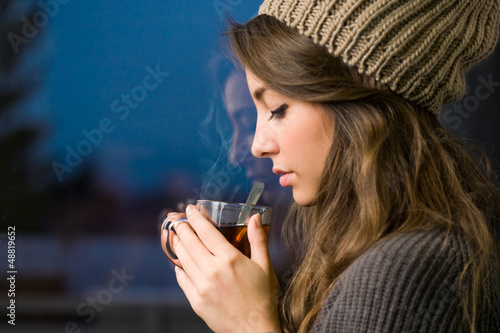Young brunette with hot tea.