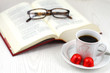 Open book, reading glasses and cup of coffee