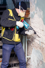 Builder hold perforator and breaks brick wall