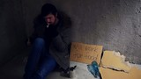 homeless sitting in the corner and smoking