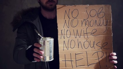 homeless hold out a tin and a cardboard