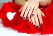 Woman hands with dark manicure lying down on red  veiling