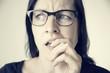 Zweifelnde Frau mit Brille