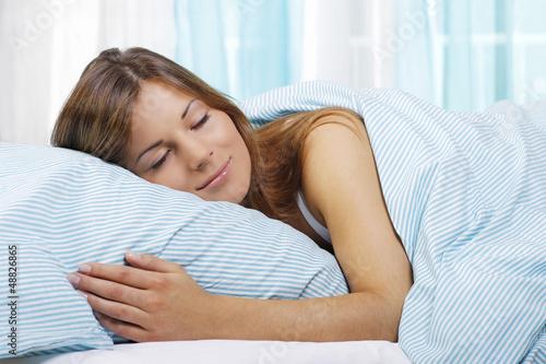 Glückliche Frau schläft im Bett