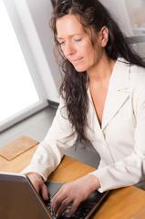 Frau arbeitet konzentriert an Notebook