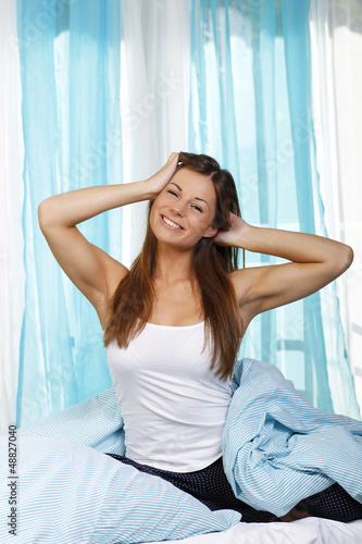 Junge Frau streckt sich morgens im Bett