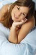 Junge hübsche Frau lächelnd im Bett