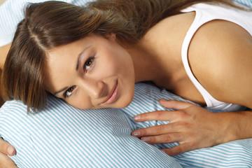 Glückliche Frau liegt im Bett den Kopf auf dem Kissen