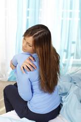 Junge Frau massiert Schulter bei Schulterschmerzen