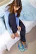 Hübsche Frau lackiert ihre Fußnägel im Bett