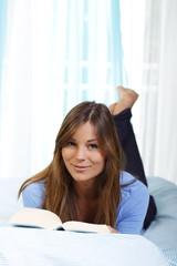 Junge Frau liestein Buch im Bett