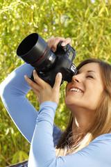 Junge Frau fotografiert mit einer teuren Spielreflexkamera