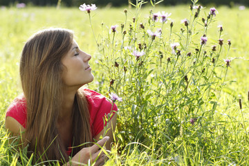 Glückliche Frau in der Wiese schaut seitlich