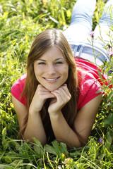 Glückliche junge Frau liegt in der Wiese auf dem Bauch