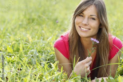 canvas print picture Glückliche Frau hält eine lila Blume in der Wiese