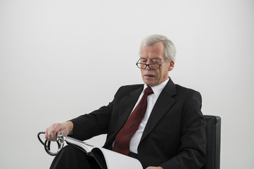 Elderly physician reading a medical journal