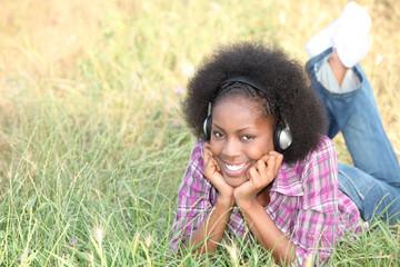 Girl lying on grass with headphones