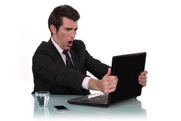 Furious businessman in front of his laptop