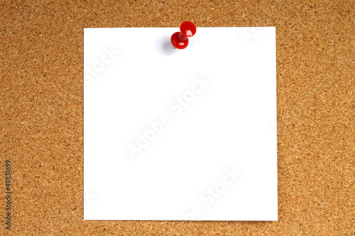 White note with pin on wooden background.