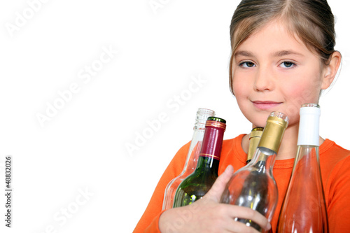 Little girl carrying glass bottles