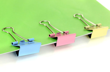 Green paper with binder clips close up