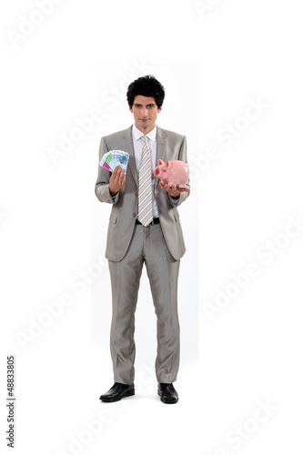 Man saving his money in a piggy bank