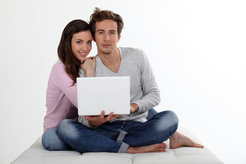 Couple using a laptop on a bed