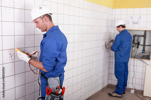 Workteam installing electrics in a tiled room