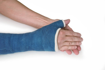 Broken wrist, arm with a blue fiberglass cast on a white backgro