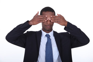 Black man covering his eyes