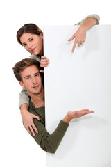Man and woman pointing to a blank board