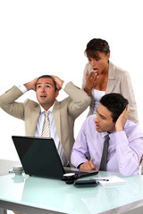 Three shocked business people looking at results