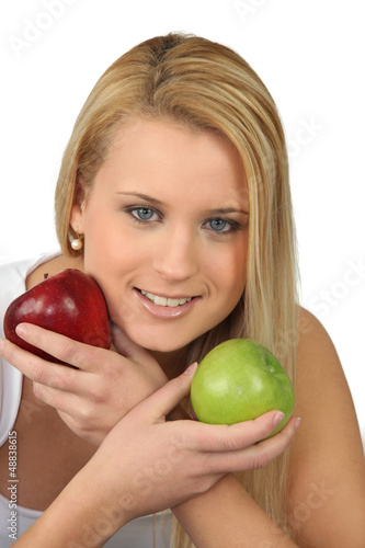 Blond woman choosing between red and green apples