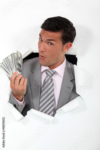 Man with banknotes of paper coming out of hole