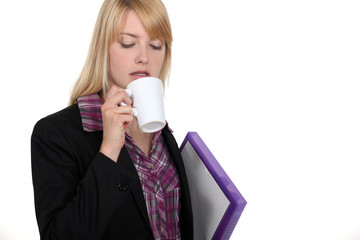 Blond worker carrying folder and coffee