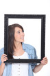 Woman stood holding empty picture frame