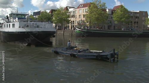 Barge with canal work boat maneuvering into dock