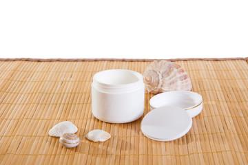 Empty cream jar on bamboo mat