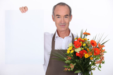 Male florist holding message board