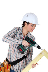 Woman constructing wooden frame